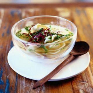 Heldere groene kruidenbouillon met tortellini en radicchio